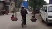 實拍男子邊騎車扁挑扁擔 扁擔里竟然還坐著兩個孩子