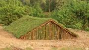生存牛人早建造了半地下庇护所,用竹子做门,用草皮装饰太美了